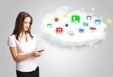 Mujer joven que presenta la nube con los iconos coloridos y los símbolos del app Imágenes de archivo libres de regalías