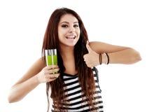 Mujer joven que presenta a un vidrio una bebida natural aislada en blanco Imagenes de archivo