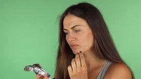 Mujer joven que prueba el chocolate oscuro, pareciendo decepcionado almacen de video