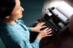 Mujer joven que pulsa con la máquina de escribir vieja Imágenes de archivo libres de regalías