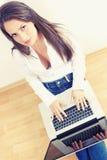 Mujer joven que pulsa en el ordenador portátil Imágenes de archivo libres de regalías