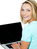 Mujer joven que pulsa en la computadora portátil Imágenes de archivo libres de regalías