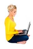 Mujer joven que pulsa en la computadora portátil Fotos de archivo