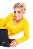 Mujer joven que pulsa en la computadora portátil Fotografía de archivo libre de regalías