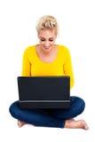 Mujer joven que pulsa en la computadora portátil Foto de archivo