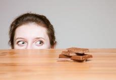 Mujer joven que quiere comer el chocolate con leche Fotos de archivo
