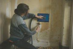 Mujer joven que quita el papel pintado imagen de archivo libre de regalías