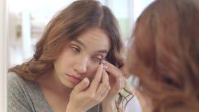 Mujer joven que quita las lentes de contacto para los ojos en el espejo en el cuarto de baño casero almacen de metraje de vídeo
