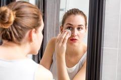 Mujer joven que quita maquillaje con la esponja delante del espejo Imagen de archivo