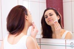 Mujer joven que quita maquillaje en cuarto de baño Foto de archivo libre de regalías