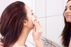 Mujer joven que quita maquillaje en cuarto de baño Foto de archivo