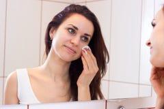 Mujer joven que quita maquillaje en cuarto de baño Fotografía de archivo
