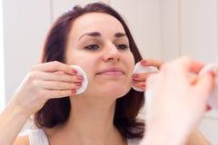 Mujer joven que quita maquillaje en cuarto de baño Fotos de archivo libres de regalías