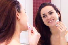 Mujer joven que quita maquillaje en cuarto de baño Imagenes de archivo