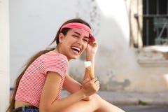 Mujer joven que ríe afuera con el cono de helado Foto de archivo