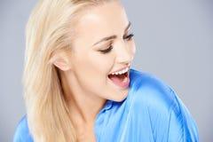 Mujer joven que ríe como ella mira abajo imagen de archivo