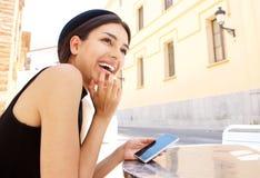 Mujer joven que ríe con el teléfono móvil Fotografía de archivo