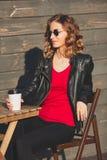 Mujer joven que ríe en vidrios redondos y una chaqueta de cuero negra Imagen de archivo
