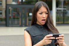 Mujer joven que reacciona en horror a SMS Imagenes de archivo