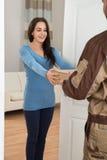 Mujer joven que recibe el mensajero de hombre de entrega Imagen de archivo libre de regalías