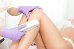 Mujer joven que recibe el tratamiento del laser del epilation Foto de archivo libre de regalías