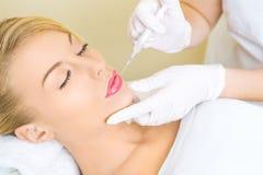 Mujer joven que recibe la inyección del botox en labios Foto de archivo