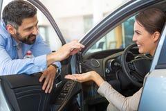 Mujer joven que recibe llaves de un concesionario de coches Imagen de archivo libre de regalías