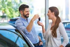 Mujer joven que recibe llaves de un concesionario de coches Fotos de archivo libres de regalías