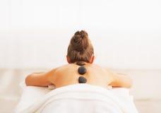 Mujer joven que recibe masaje de piedra caliente. vista posterior Foto de archivo