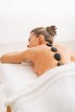 Mujer joven que recibe masaje de piedra caliente. vista posterior Imagen de archivo libre de regalías