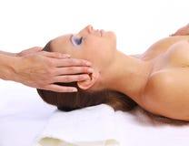 Mujer joven que recibe masaje facial Imagen de archivo libre de regalías