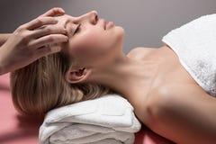 Mujer joven que recibe masaje facial Foto de archivo libre de regalías