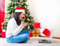 Mujer joven que recibe un regalo de Navidad sobre el ordenador portátil Foto de archivo libre de regalías