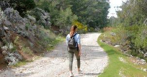 Mujer joven que recorre en el camino almacen de metraje de vídeo