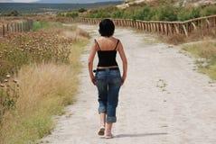 Mujer joven que recorre en el camino en el campo Imágenes de archivo libres de regalías