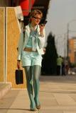 mujer joven que recorre en la calle y que habla en el teléfono Foto de archivo libre de regalías