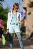 Mujer joven que recorre en la calle y que habla en el teléfono Fotografía de archivo libre de regalías