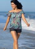 Mujer joven que recorre en la playa imagenes de archivo