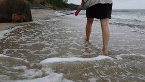 Mujer joven que recorre a lo largo de la playa metrajes