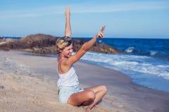 Mujer joven que reflexiona sobre la playa, embarcadero en la posición de loto en el sunri foto de archivo libre de regalías