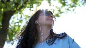 Mujer joven que relaja al aire libre escuchar la música y la sonrisa imagenes de archivo