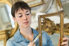 Mujer joven que renueva el marco antiguo imagenes de archivo