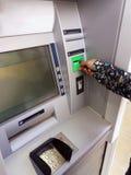 Mujer joven que retira el dinero de la tarjeta de crédito en la atmósfera fotografía de archivo