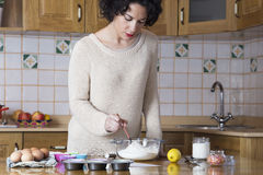 Mujer joven que revisa los ingredientes de una receta para las magdalenas Foto de archivo libre de regalías