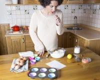 Mujer joven que revisa los ingredientes de una receta para las magdalenas Imágenes de archivo libres de regalías