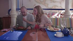 Mujer joven que roba la comida de su placa del ` s del novio en un restaurante El hombre es ceño fruncido metrajes