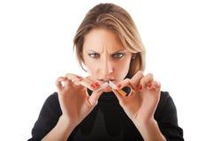 Mujer joven que rompe el cigarrillo Imagen de archivo libre de regalías