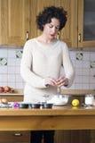 Mujer joven que rompe un huevo que hace las magdalenas Imagenes de archivo