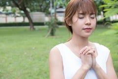 Mujer joven que ruega en parque público la muchacha asiática dobló sus manos Foto de archivo