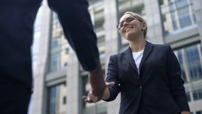 Mujer joven que sacude la mano con el jefe, la enhorabuena con el alquiler o la promoción almacen de video